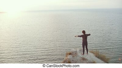 Young woman doing morning warm-up on rocky cliff by the river