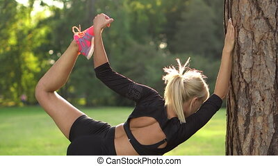young woman doing muscle stretching near tree in nature on a...