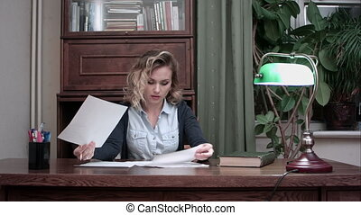 Young woman doing paperwork in the office sitting at her desk