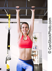 Young woman doing pull-ups in the gym