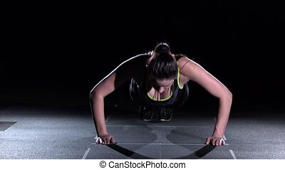 Young woman doing push-ups in a gym, on black