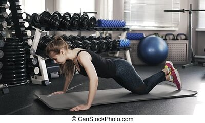 Young woman doing push ups in a gym, side view