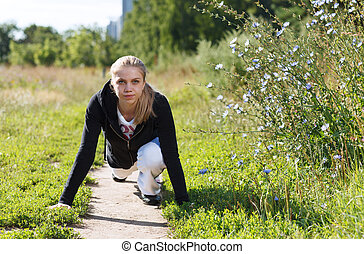 Young woman doing push ups in the park