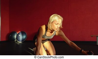 Young woman doing push-ups. Muscular female doing pushups on exercise mat.