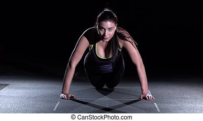 Young woman doing push-ups on her knees in a gym, on black