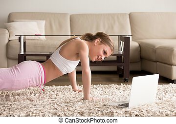 Young woman doing push-ups on in living room
