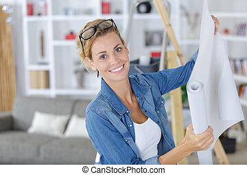 young woman doing repairs in apartment wallpapering on wall