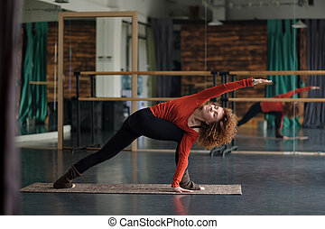 Young woman doing revolved side angle pose, parivrtta parsvakonasana.