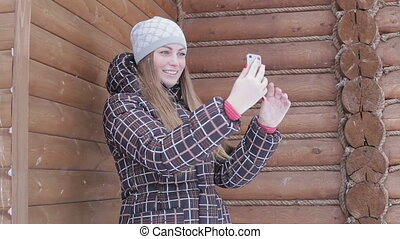Young woman doing selfie on background  house