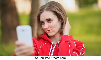 Young woman doing selfie with a white phone