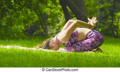 Young woman doing shashankasana in the park