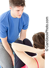 Young woman doing sit-ups assited by her personal trainer