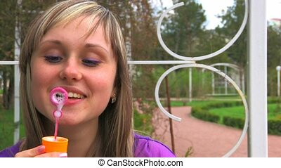 Young woman doing soapbubbles