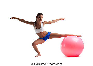 Young woman doing split with fitness ball isolated
