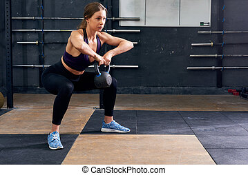 Young Woman Doing Squats with Weights
