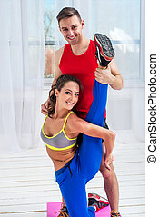 Young woman doing streching exercises with man smiling looking at camera concept training exercising workout fitness aerobic