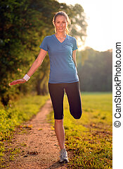 Young woman doing stretching exercises as she limbers up her muscles to go on a jog or begin a workouts standing over a country track in golden light smiling at the camera
