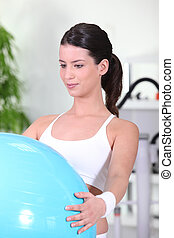 young woman doing Swiss ball exercises