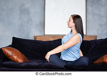Young woman doing the spine twisting pose sitting at home on sofa.