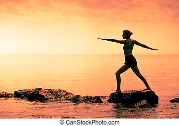 Young Woman doing the Warrior Yoga Position in Front of the Ocean
