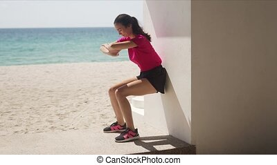 Young woman doing wall squats on beach - Side view of slim ...