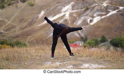 Young woman doing warm-up in hilly terrain. Adult female in black casual clothes doing sports in fresh air in countryside