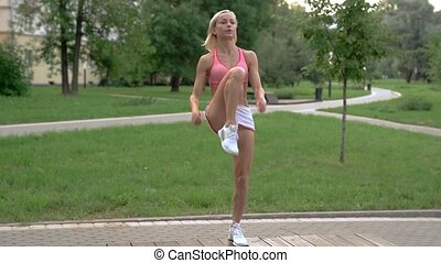 Young woman doing workout in park on a bench