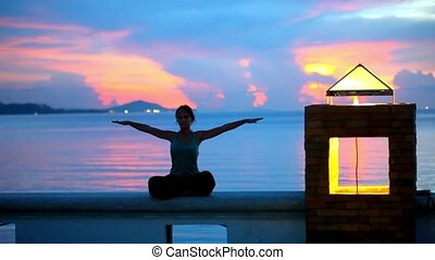 Young woman doing yoga and meditates over the sunset background