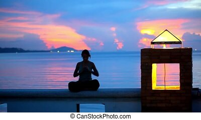 Young woman doing yoga and meditates over the sunset background.