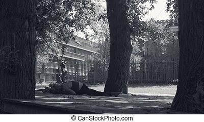 Young woman doing yoga asana - janu-shirshasana in the park...