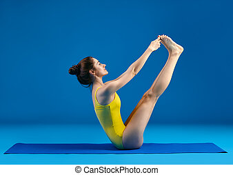young woman doing yoga asana supported headstand young