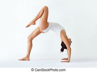 Young woman doing yoga asana bridge pose with right leg up....