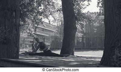 Young woman doing yoga asana - kurmasana in the park at...