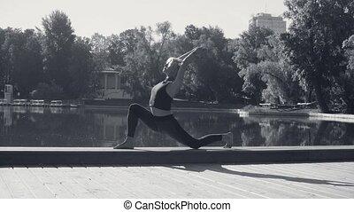 Young woman doing yoga asana - virasana - in the park...