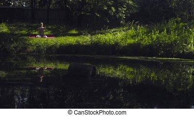 Young woman doing yoga asanas on the river bank