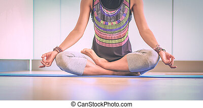 Young woman doing yoga at home in the lotus position
