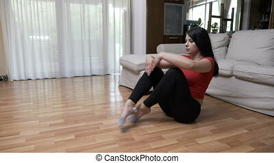 Young woman doing yoga breathing exercise and meditating in lotus position on the floor at home