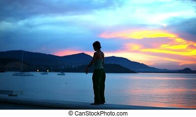 Young woman doing yoga bridge, sunset silhouette on island, Thailand. Sport and fitness stretching exercising outdoors in nature.