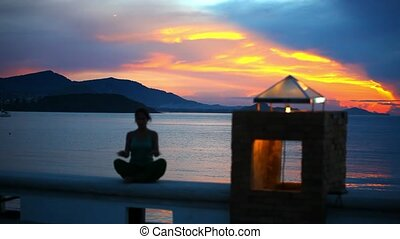 young woman doing yoga exercise in and meditates on a background sunset.