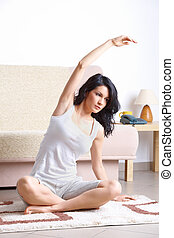Young woman doing yoga exercise on mat - Portrait of fit ...