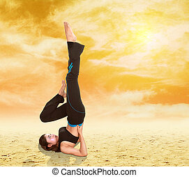 woman doing yoga exercise on sand with sky at sunset