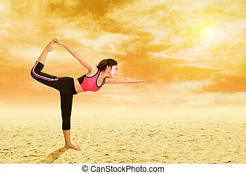 Young woman doing yoga exercise on sand with sky