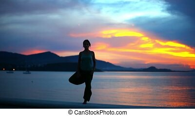 young woman doing yoga exercise on the background of sunset.