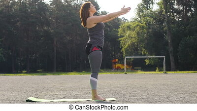 Young woman doing yoga exercise outdoors - Overweight young...