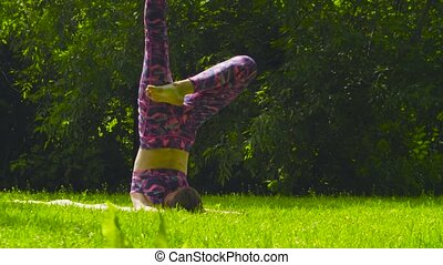 young woman doing yoga asana  virasana  in the park