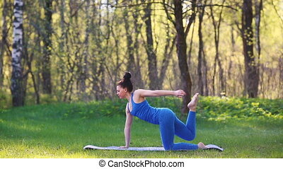 Young woman doing yoga exercises in the summer city park. Health lifestyle concept.