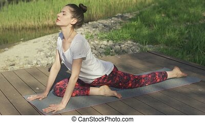 Young woman doing yoga exercises on mat in summer day -...