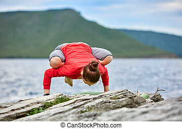 Young woman doing yoga exercises on stone near big river against beautiful landscape.