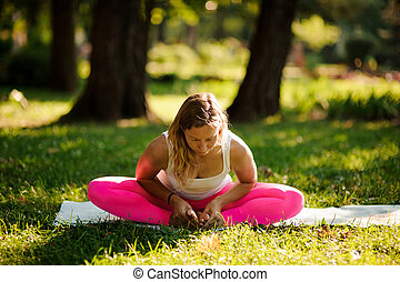 Young woman doing yoga exercises on the grass
