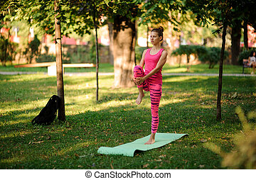 Young woman doing yoga exercises on the grass in a park